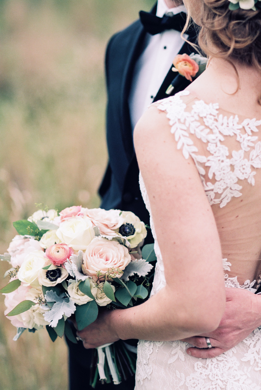 Detail of back of bride's dress and bridal bouquet.