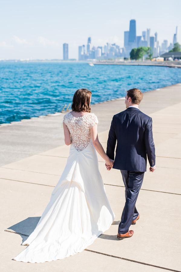 Bride and groom walking along Lake Michigan at Diversey Harbor.