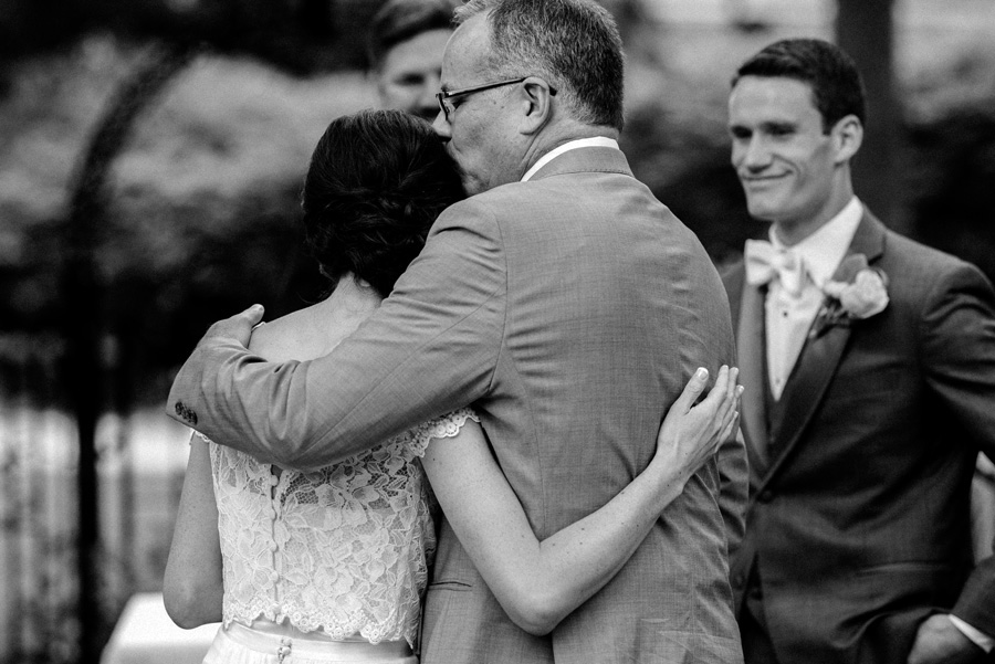 Dad kisses his daughter at wedding ceremony.