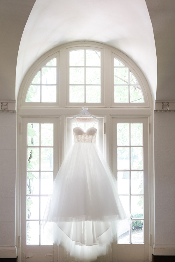 Wedding dress hanging up in window.
