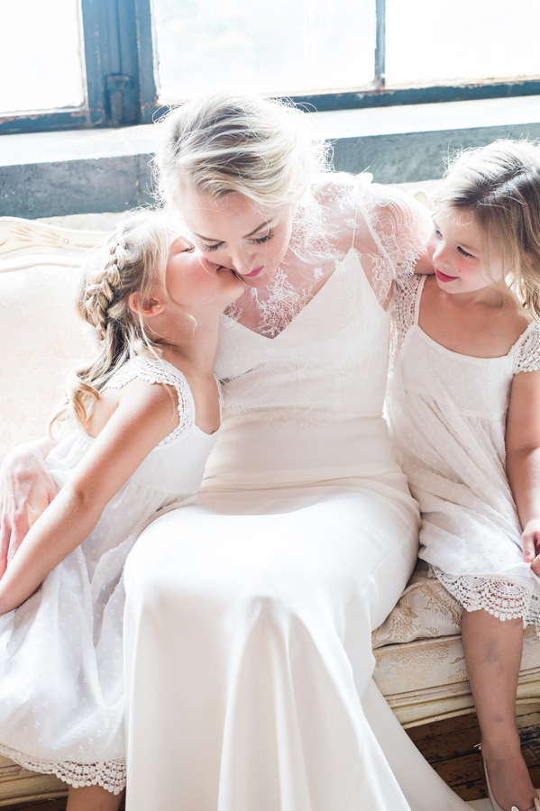 Bride gets a kiss from her flower girls.