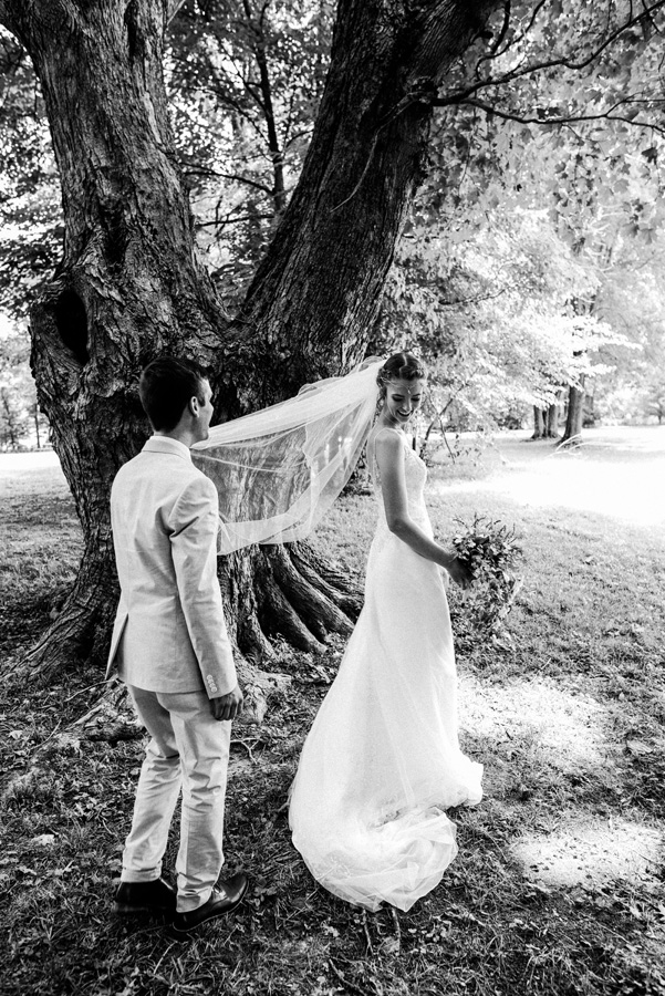 Bride and groom first look under an old tree.