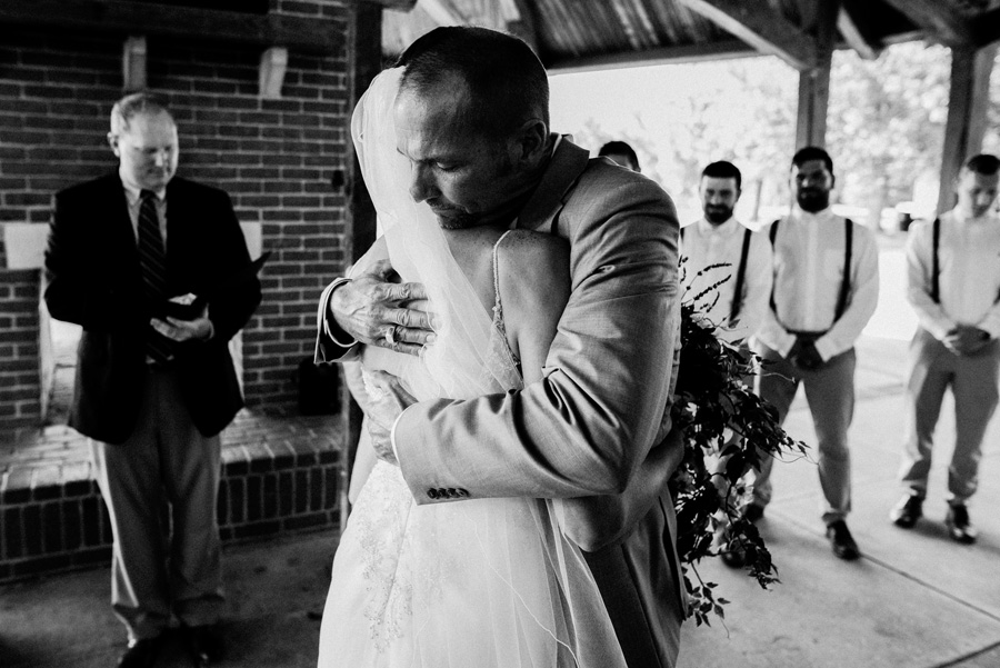 Bride hugs her dad at her wedding ceremony.