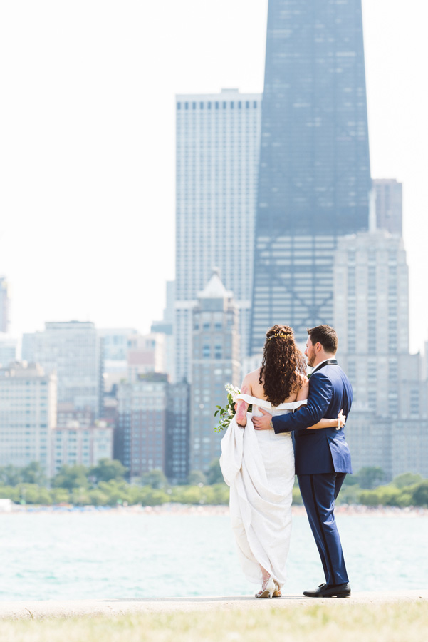 Bride and groom looks at skyline at North Ave Beach, Chicago.