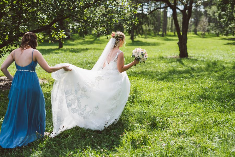 Bride walking through a field.