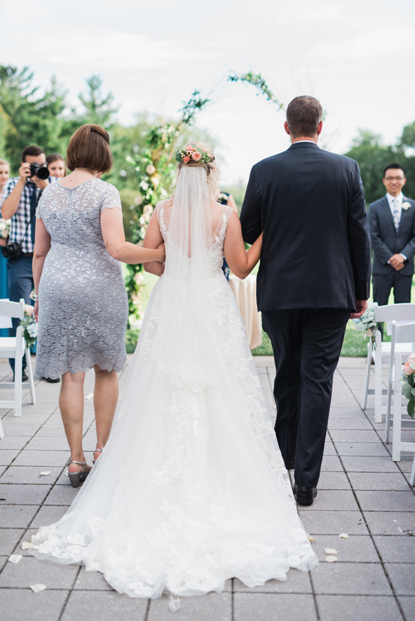 Bride walks down the aisle with her parents.