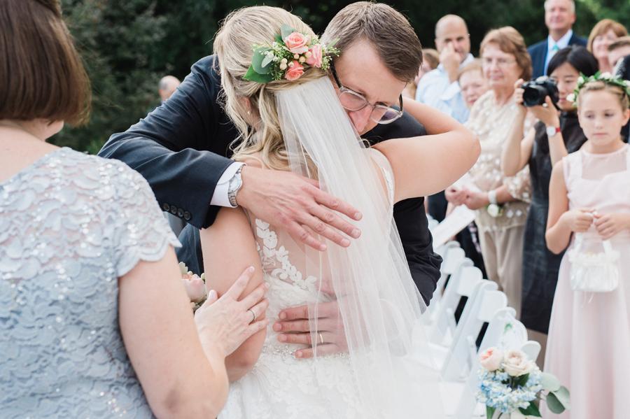 Bride hugs her dad at wedding ceremony.