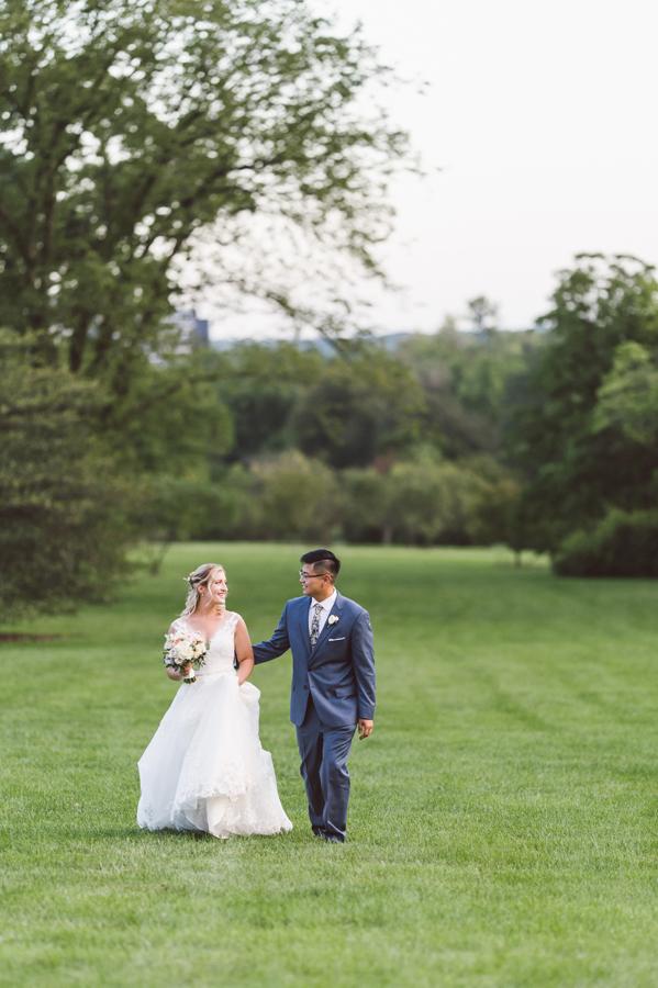 Bride and groom walk in field.