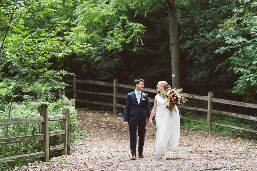 Bride and groom walk along a forest path.