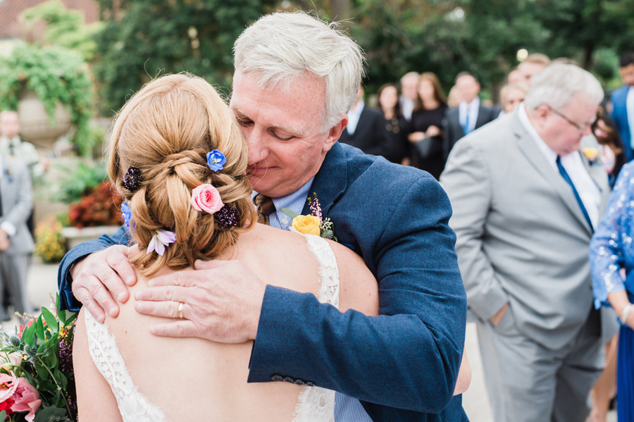 Dad hugs his daughter at wedding ceremony.