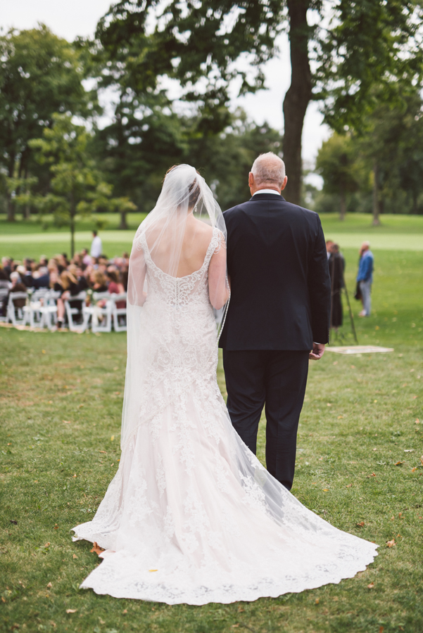 Bride walks down the aisle with her dad.