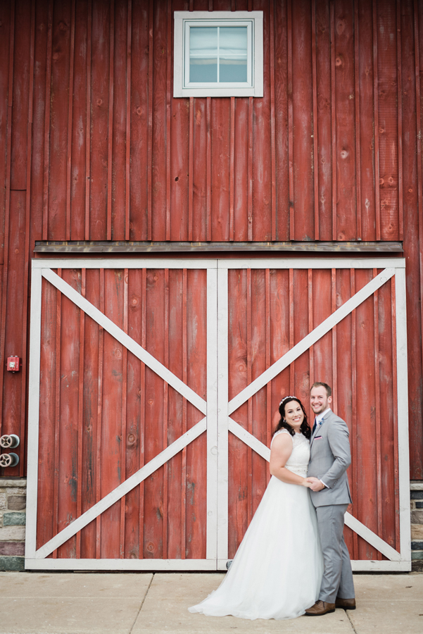 Portrait of bride and groom in front of barn.