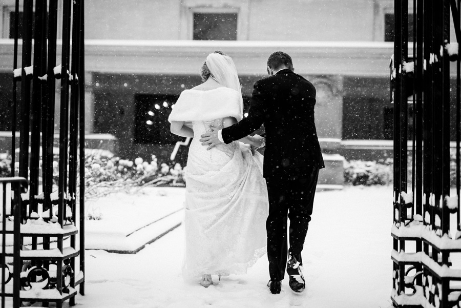 Bride and groom walk on snowy path.