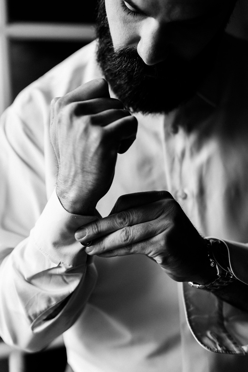 Groom putting cufflinks on.