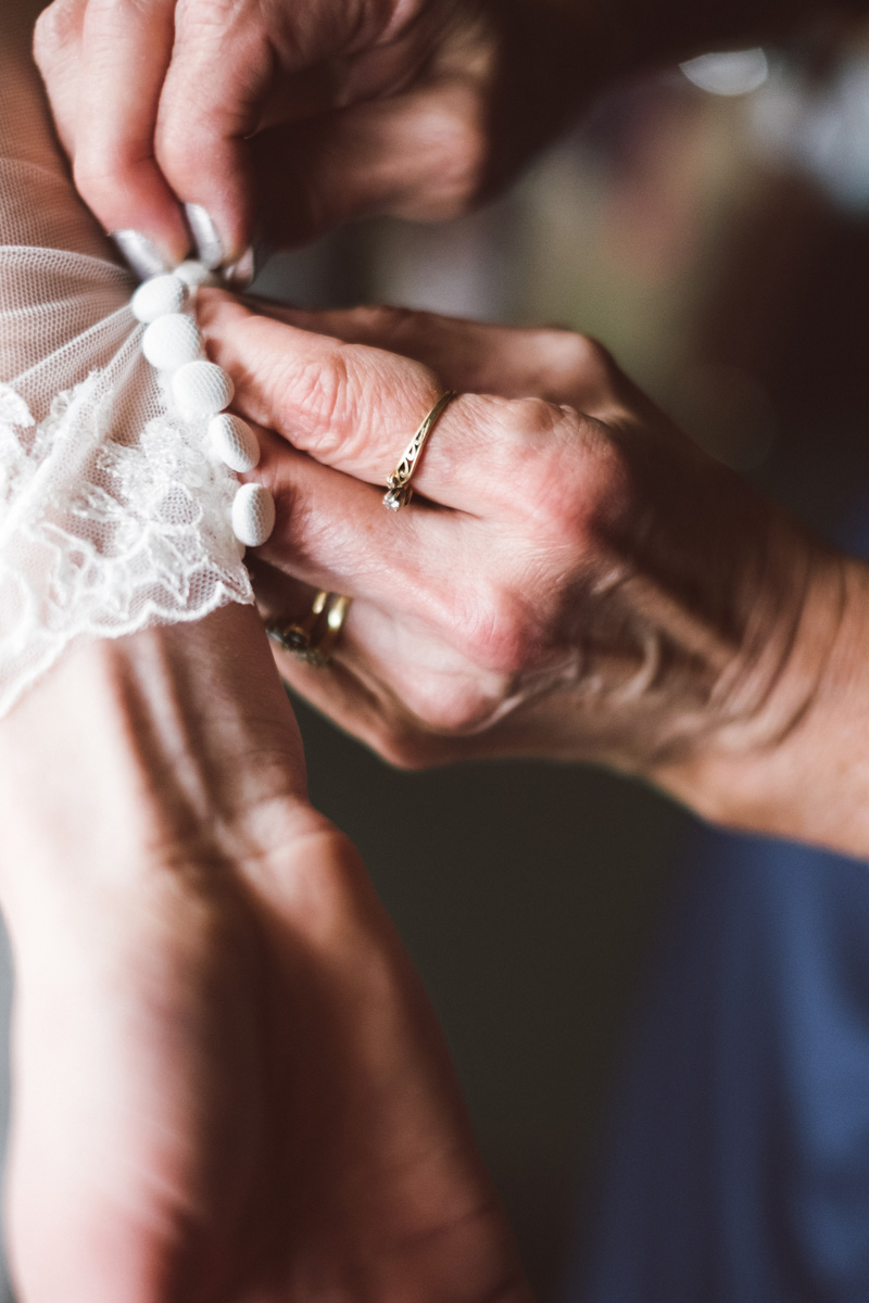 Mom helping bride with her dress.