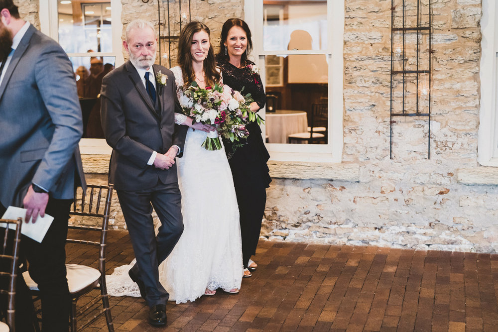 Bride walks in with her parents at ceremony.
