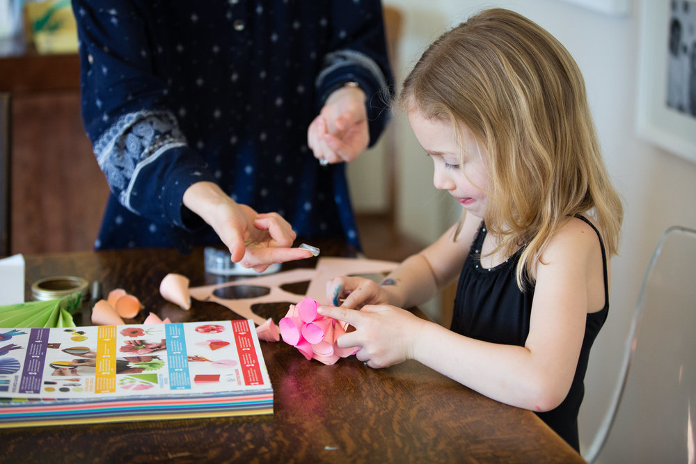 mom helps daughter with crafts