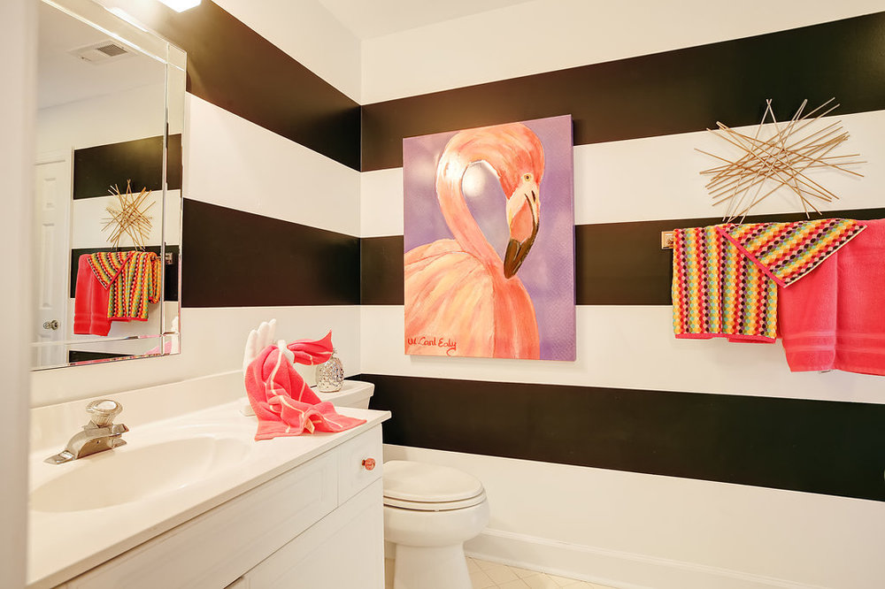 Bathroom with bland and white striped walls and flamingo art.