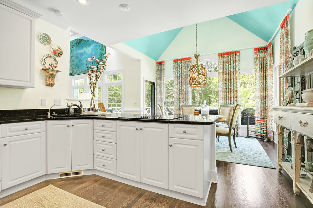 Transitional kitchen with white cabinets and dark countertops