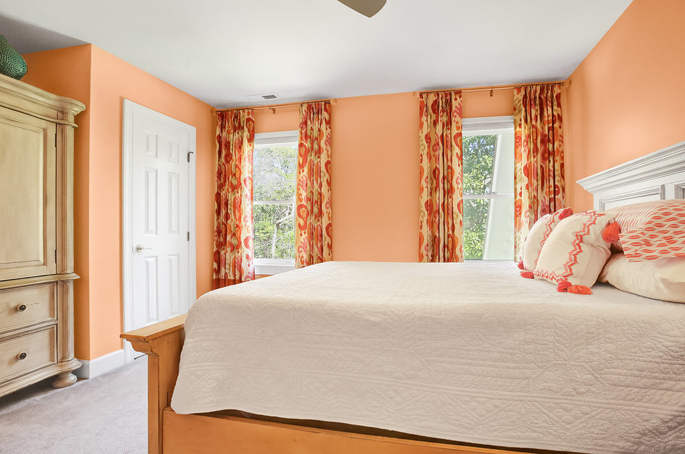 Coral colored bedroom with patterned drapes