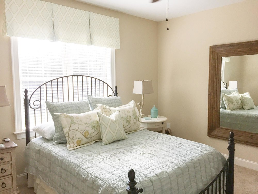 Guest bedroom with floral pillow shams and wooden mirror hanging on wall