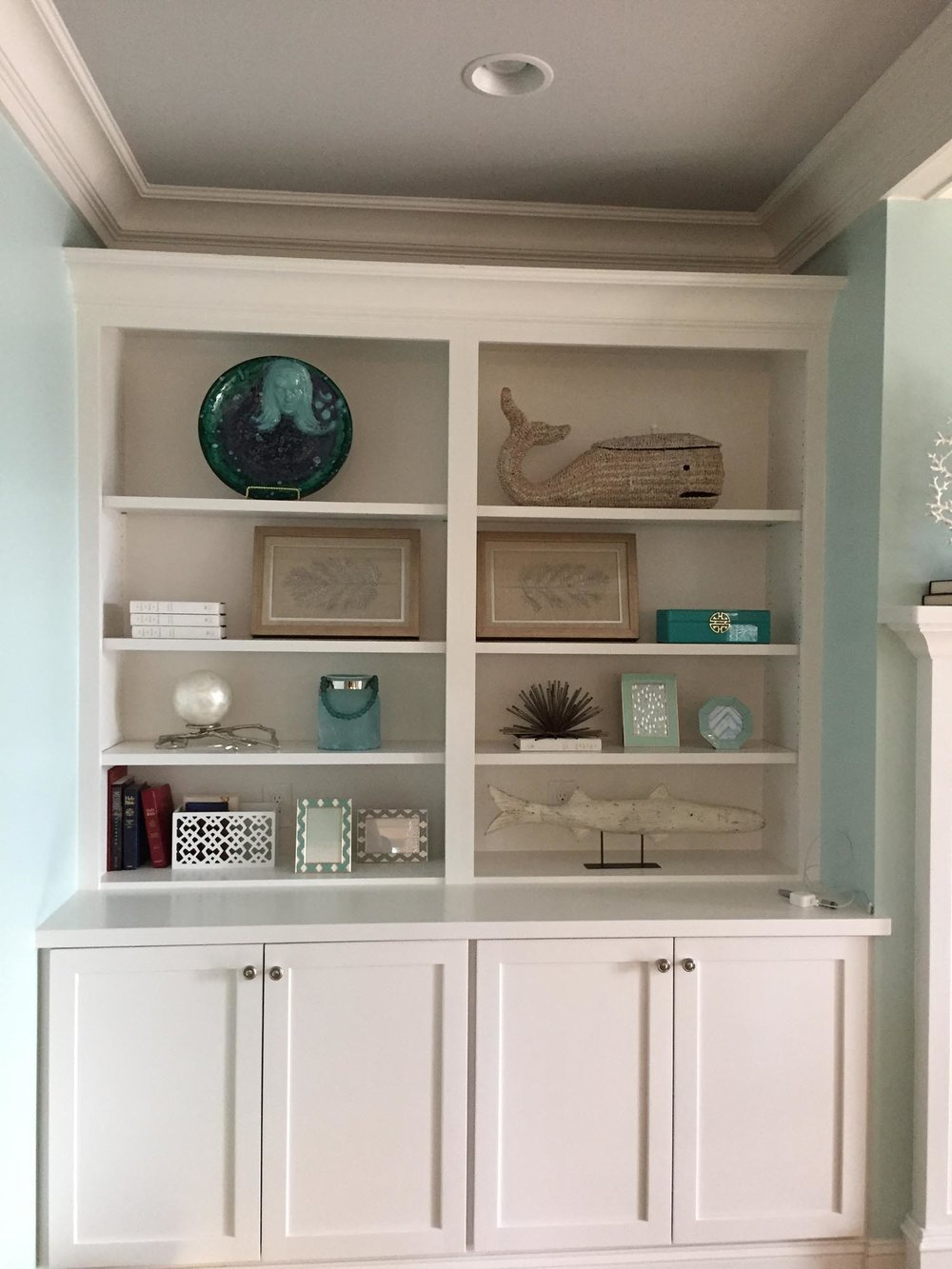 White built in book case with fish accessories and framed art