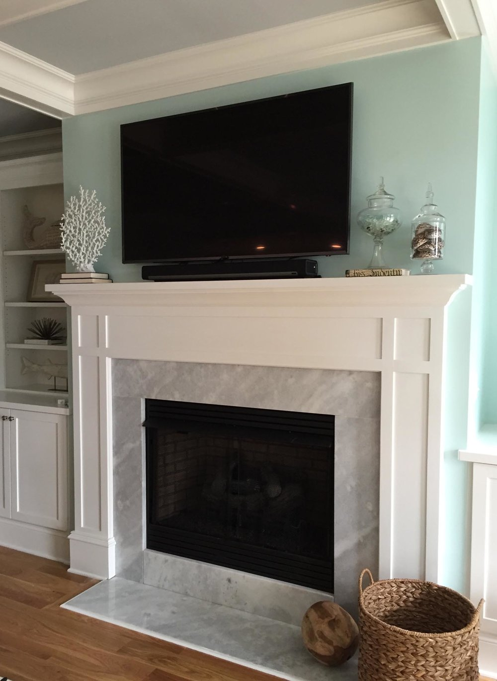 Marble grey and white fireplace with sea glass jar on mantle piece