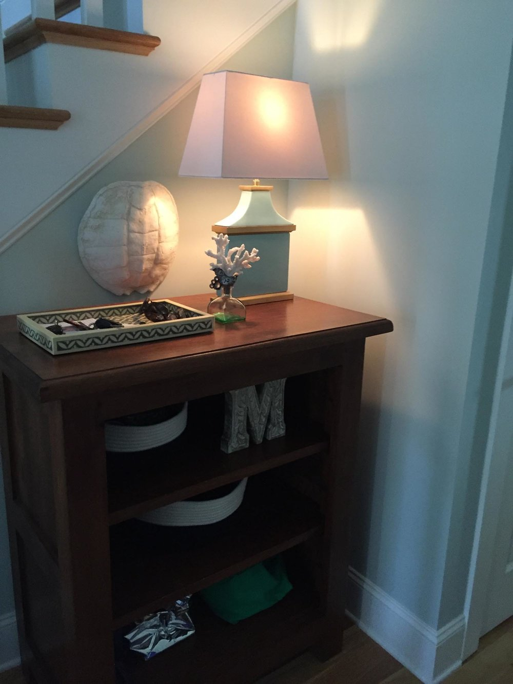 Blue and gold lamp on wooden shelving with turtle shell art on wall