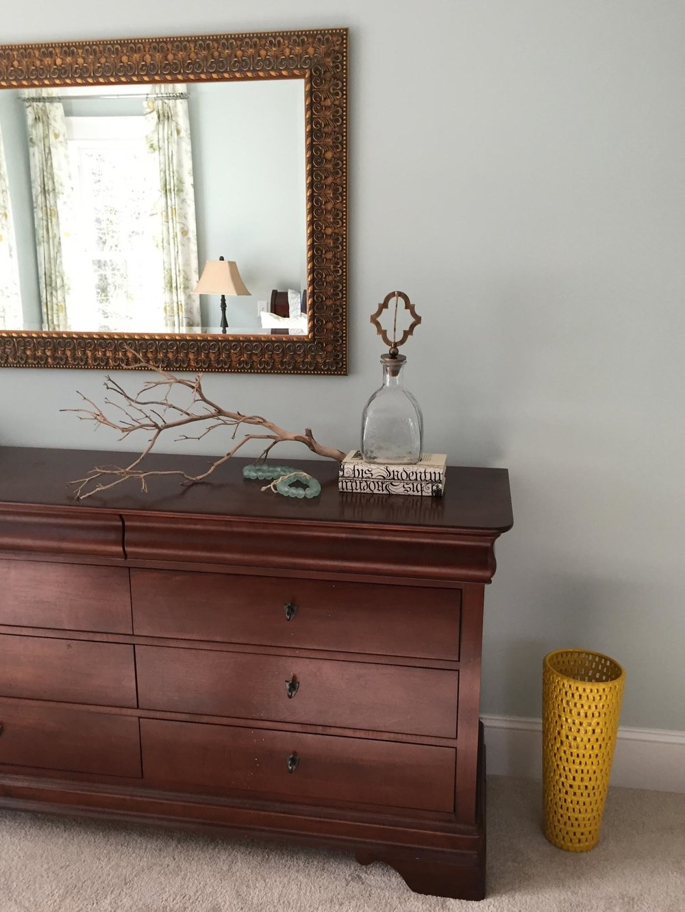 Coastal inspired accessories on oak dresser with hanging mirror