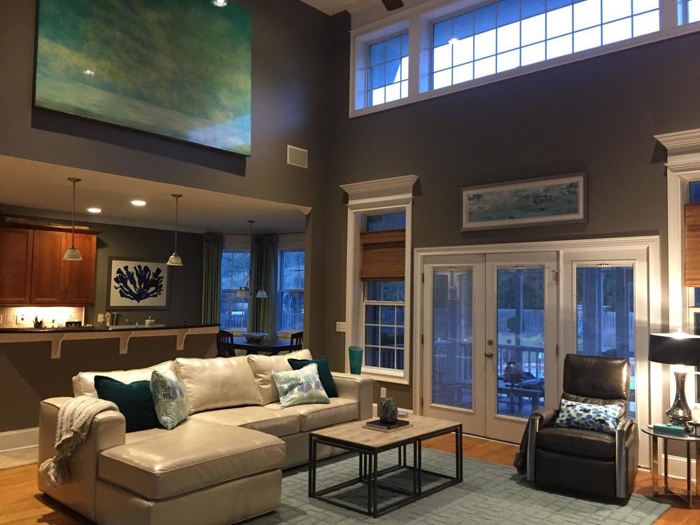 Open concept living area with large abstract green colored landscape hanging high on vaulted wall