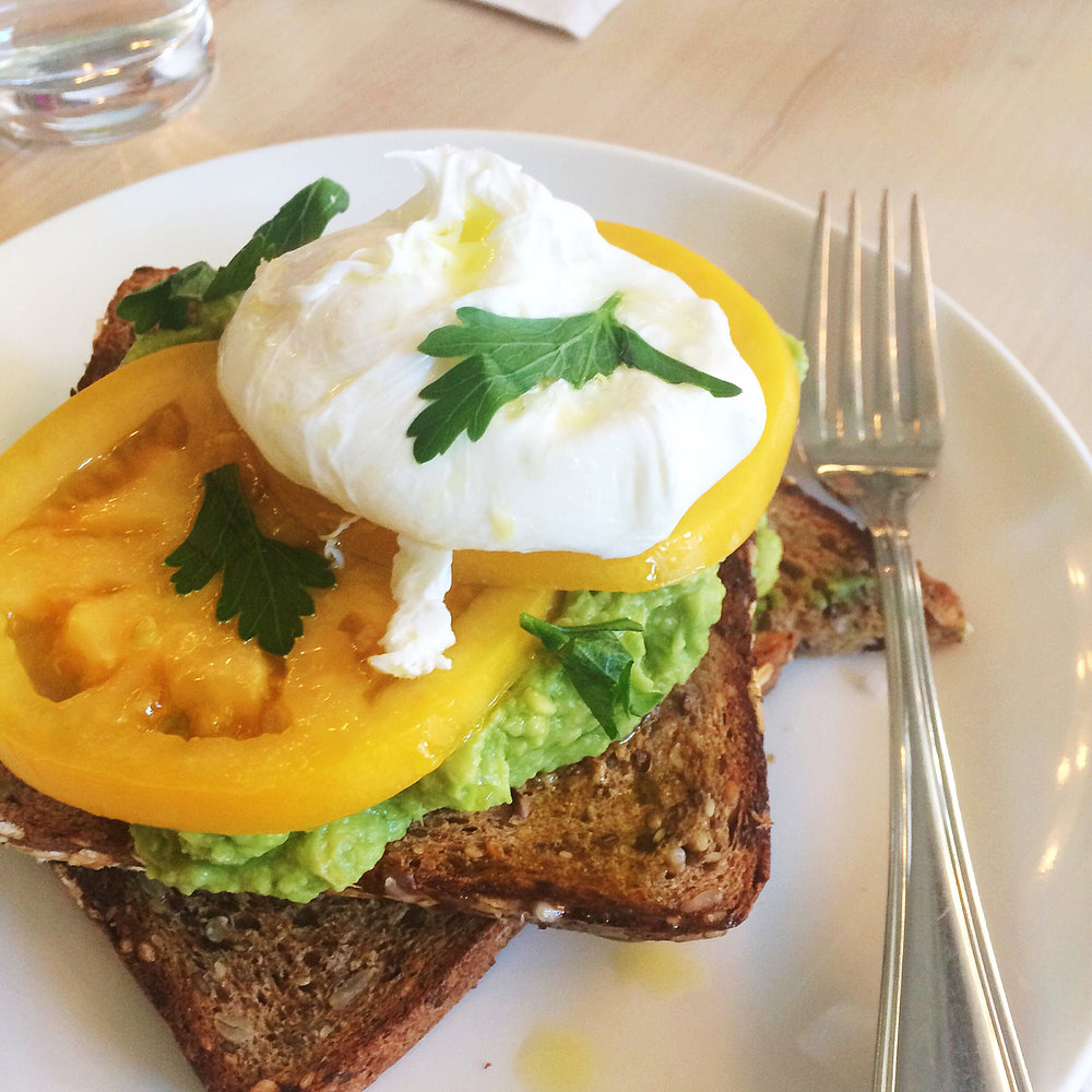 Avocado toast with heirloom tomatoes and a poached egg