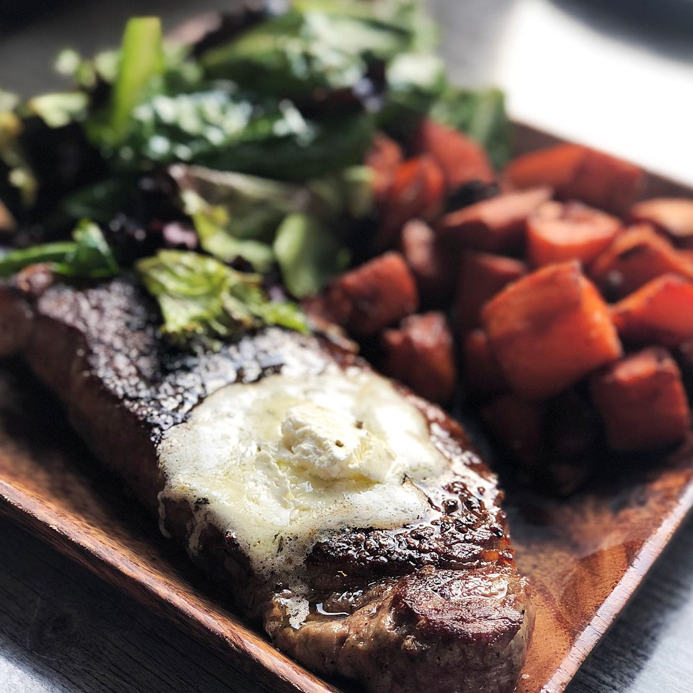 The Steak board from Meat and Cheese: butcher's cut with rosemary butter, roasted sweet potatoes, and lightly dressed greens.