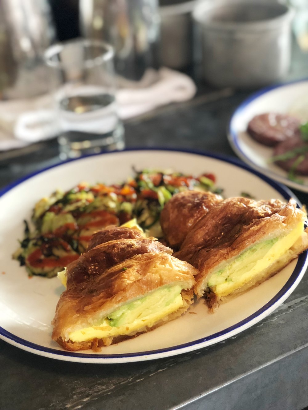Egg croissant sandwich with sriracha brussels sprouts