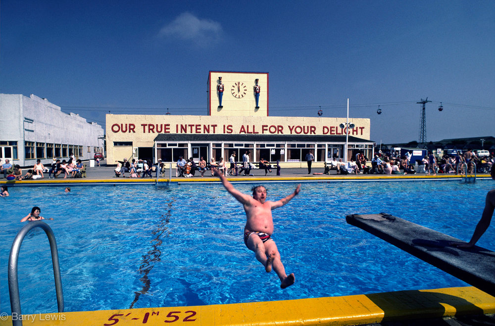 Man falling into swimming pool in Butlins holiday camp, Skegness, UK, 1982. The slogan 'Our true intent is all for your delight'. was borrowed by Billy Butlin from Shakespere's play, A Midsummer Night's Dream.