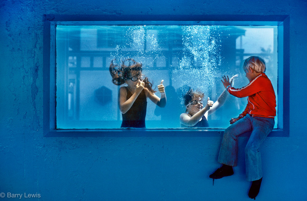 Boy watching the underwater swimmers through  the swimming pool window. Butlins Holiday camp, Skegness UK 1982