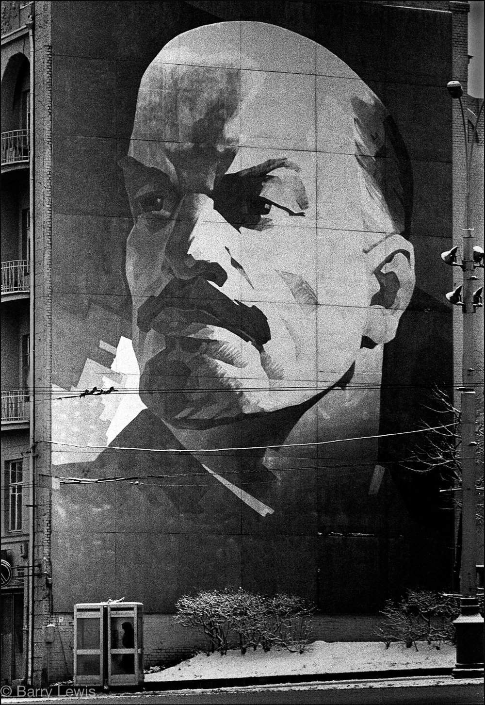 Giant mural of Lenin towering over a telephone box. Moscow, 1972