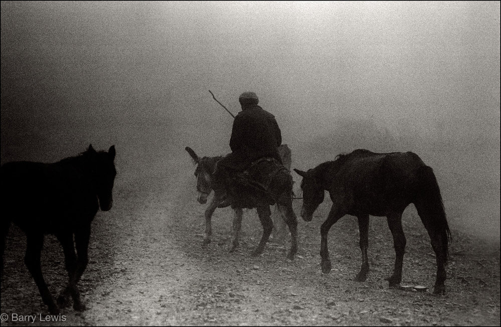Farmer riding into the winter mist along the ancient Camín Real de la Mesa, Spain 1985.