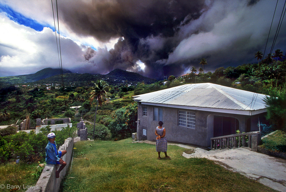 Family watching the eruption of  Chances Peak volcano in the Soufriere Hills, Monserrat, 1997.