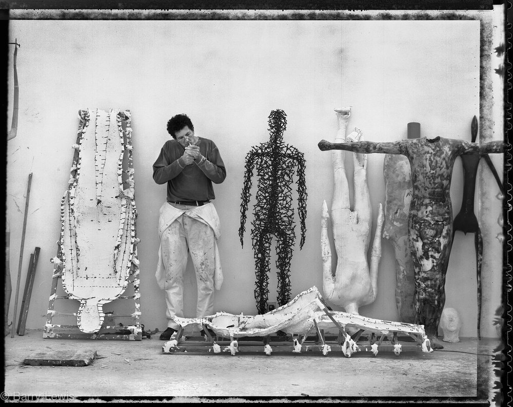 Anthony Gormley, sculptor, lighting up in his studio, London, 1999