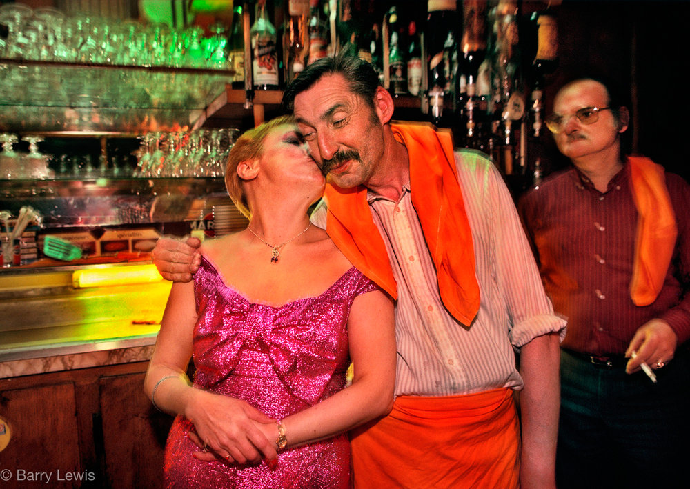 A secret kiss for the waiter in Chez Louisette, Paris, 1991. Started in the 1930s, in the heart of the flea market, by Madame Louisette and fuelled by the songs of Edith Piaf, it is a little bit of traditional Paris.