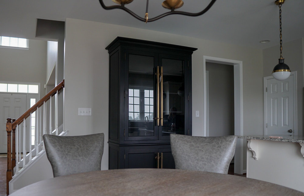 Black kitchen cabinet with brass hardware (and peek-a-boo shot of the island pendants)