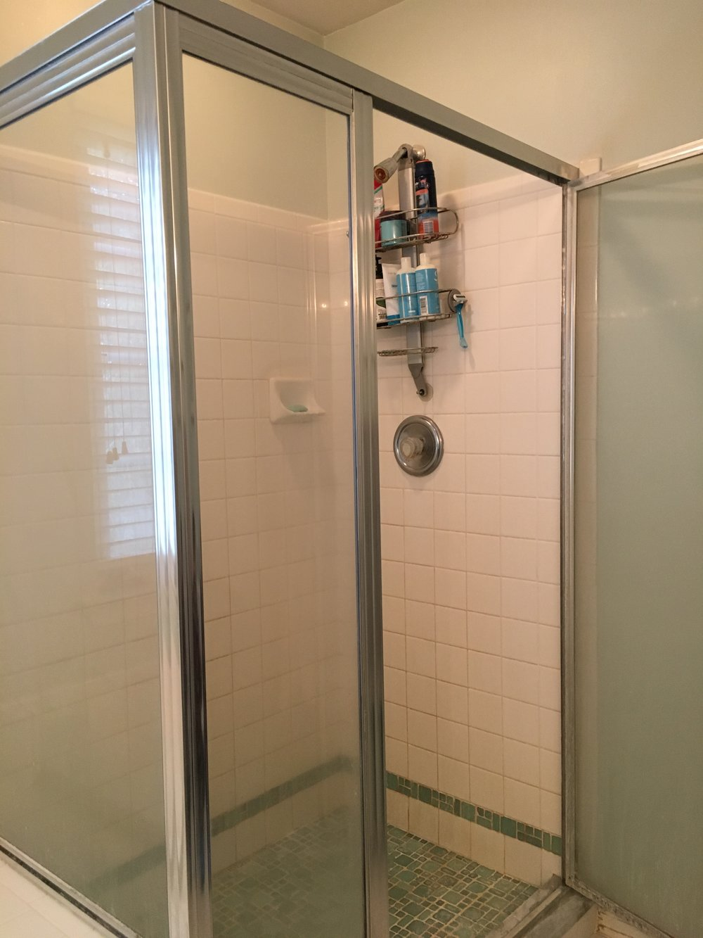 BEFORE: Tiny shower with tile that has seen better days.