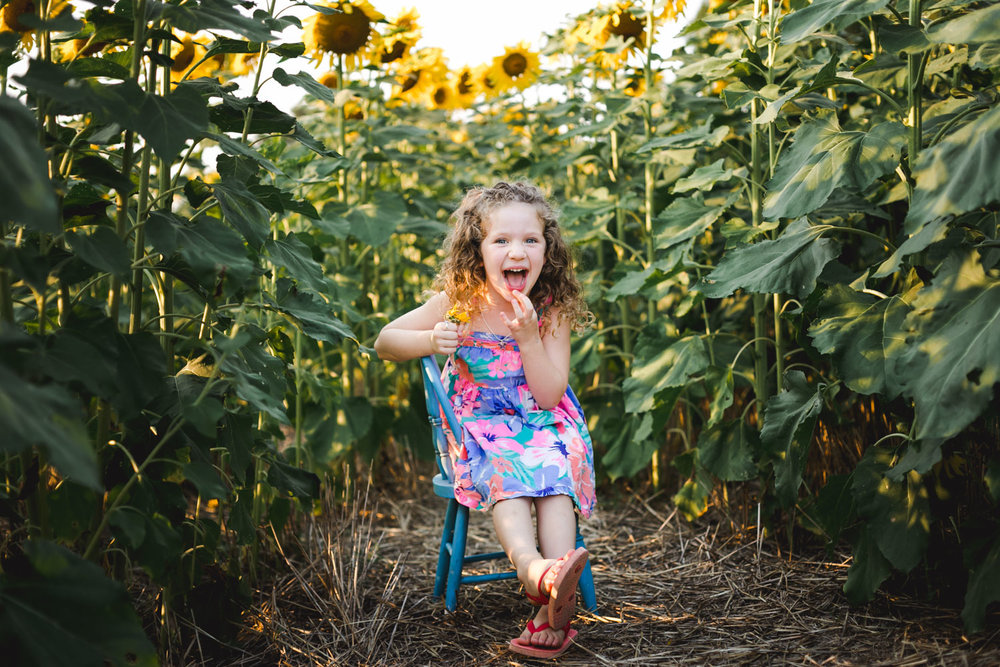 Girl sitting in the sunflower field at Kansas State University in Manhattan, Kansas. Captured by photographer, Renee McDaniel of Renee McDaniel Photography.