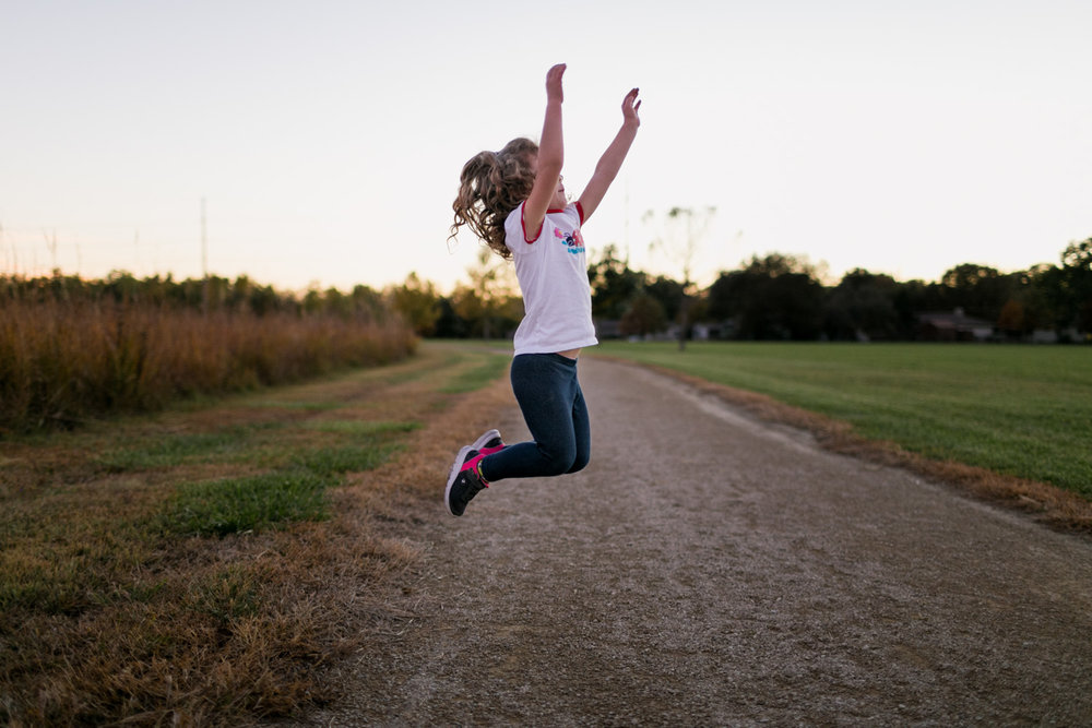 Documentary Lifestyle image of toddler jumping in the air on Linear Trail. Captured by Manhattan Kansas Photographer, Renee McDaniel