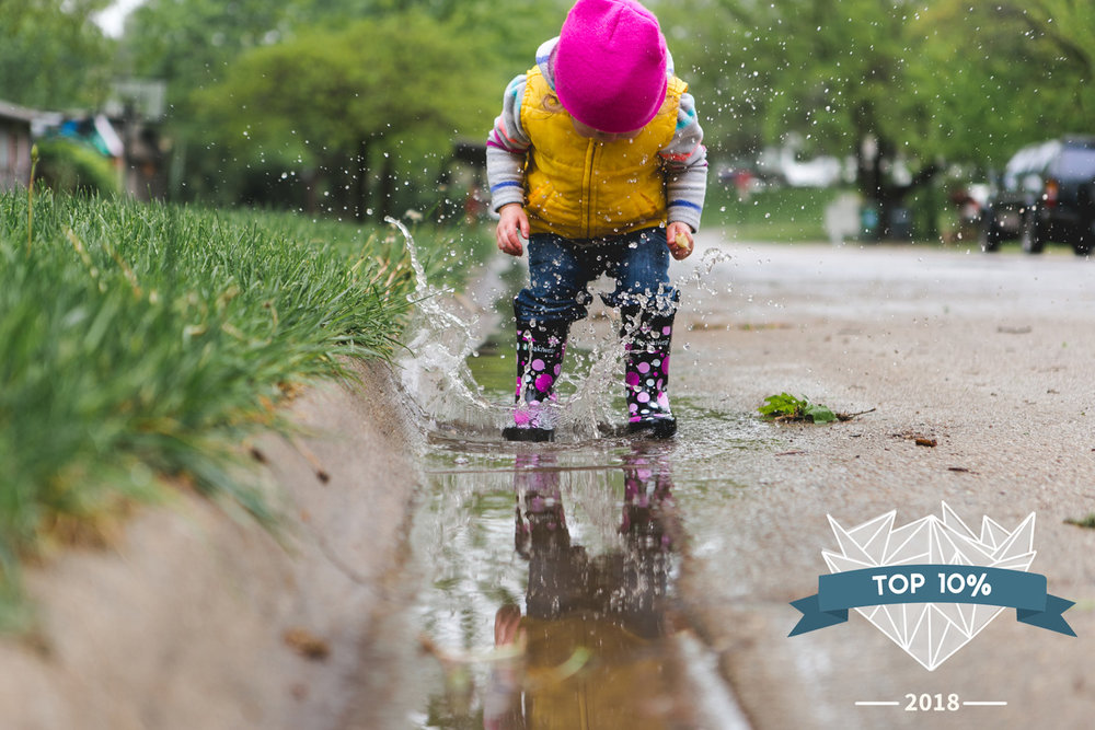Girl splashing in rain puddle after rain in Manhattan Kansas. Captured by best family and child documentary photographer, Renee McDaniel Photography.