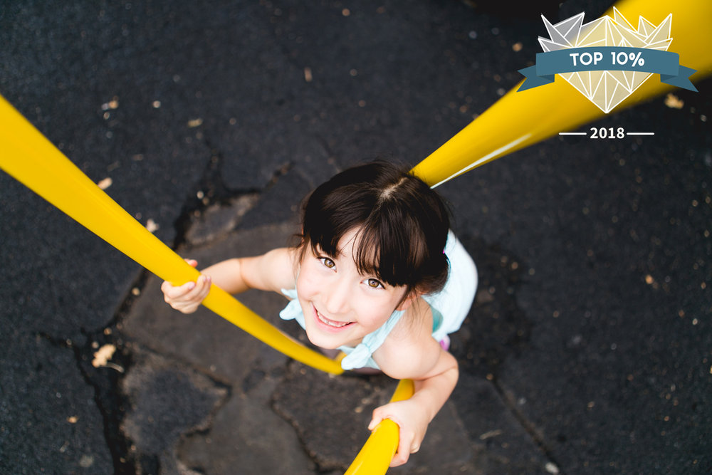 Girl playing on merry-go-round at City Park in Manhattan Kansas. Captured by best family and child photographer, Renee McDaniel Photography