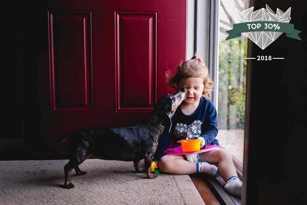 Dachshund giving little girl kisses while she sits on the floor by an open door.