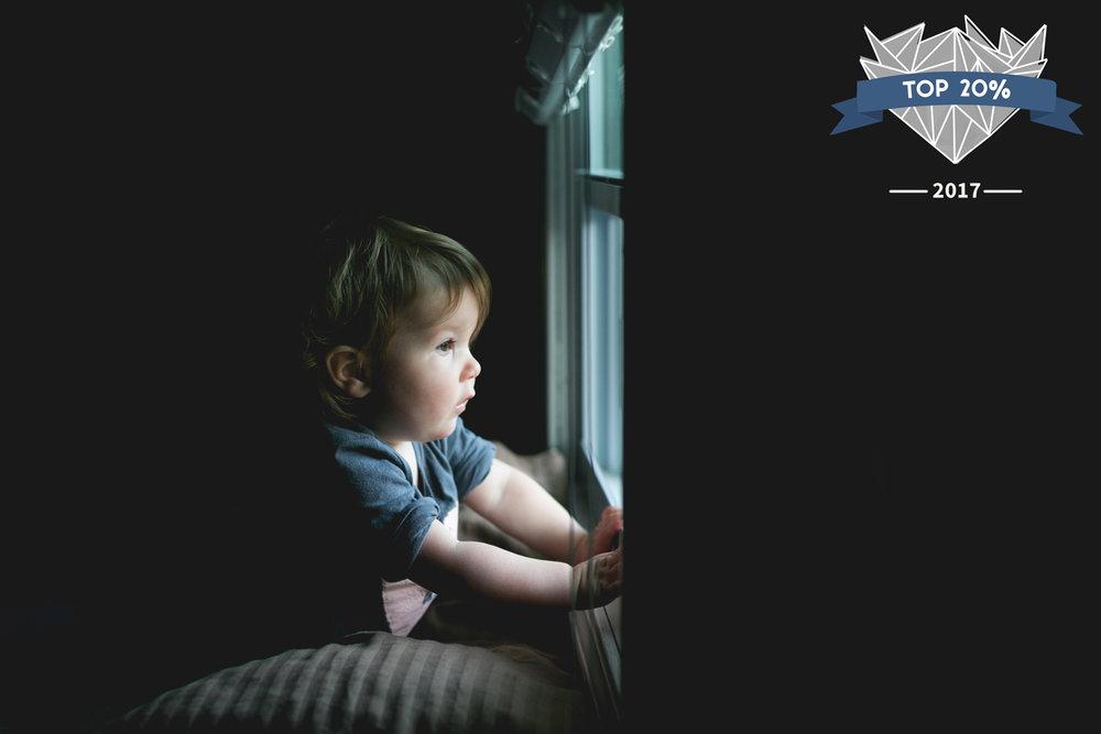 Toddler staring out window in Manhattan, Kansas.