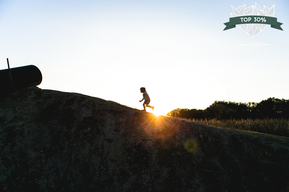 Little girl running up a hill at Britt's Garden Acres' Pumpkin Patch while the sun sets behind her. Captured by best family and child documentary photographer in Manhattan, Kansas, Renee McDaniel Photography.
