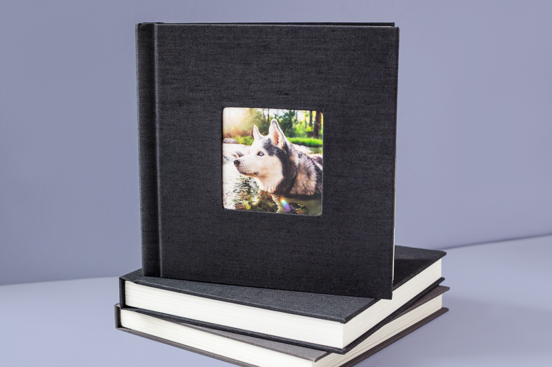 A stack of photo albums sits on a lavender-colored background.